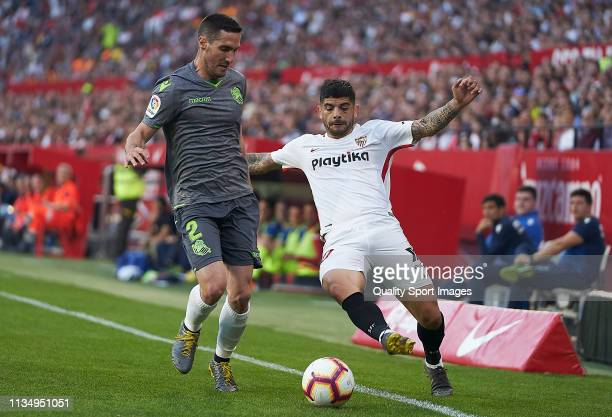 Ever Banega of Sevilla FC competes for the ball with Joseba Zaldua of Real Sociedad during the La Liga match between Sevilla FC and Real Sociedad at...