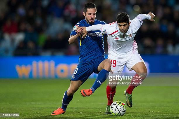 Ever Banega of Sevilla FC competes for the ball with Pablo Sarabia of Getafe CF during the La Liga match between Getafe CF and Sevilla CF at Coliseum...