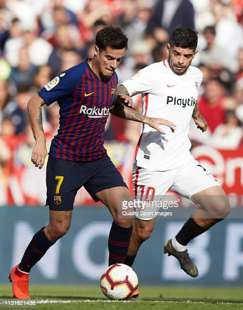 Ever Banega of Sevilla FC competes for the ball with Philippe Coutinho of FC Barcelona during the La Liga match between Sevilla FC and FC Barcelona...