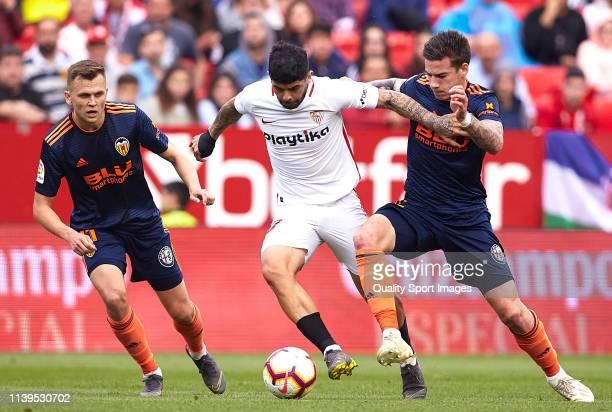 Ever Banega of Sevilla FC competes for the ball with Santi Mina of Valencia CF during the La Liga match between Sevilla FC and Valencia CF at Estadio...