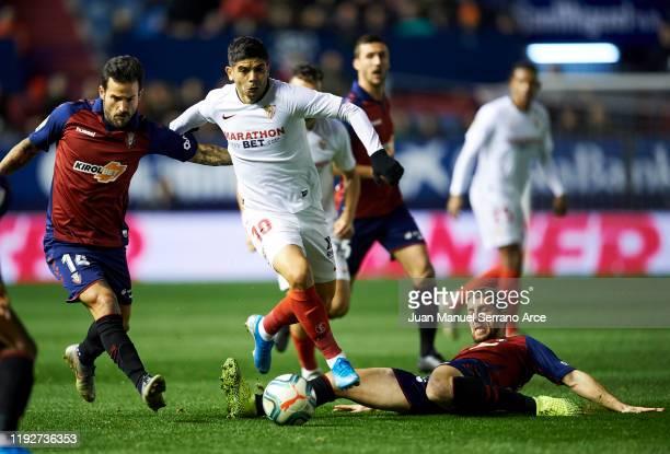 Ever Banega of Sevilla FC duels for the ball with Darko Brasanac of CA Osasuna during the Liga match between CA Osasuna and Sevilla FC at El Sadar...