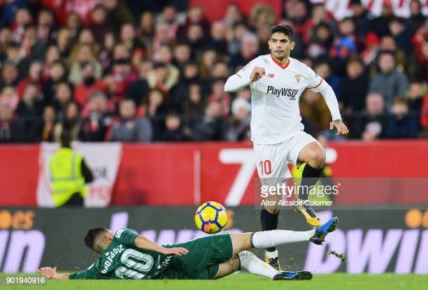 Ever Banega of Sevilla FC duels for the ball with Ryad Boudebouz of Real Betis during the La Liga match between Sevilla FC and Real Betis Balompie at...