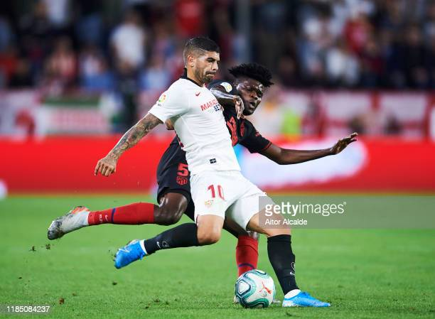 Ever Banega of Sevilla FC duels for the ball with Thomas Teye Partey of Club Atletico de Madrid during the Liga match between Sevilla FC and Club...