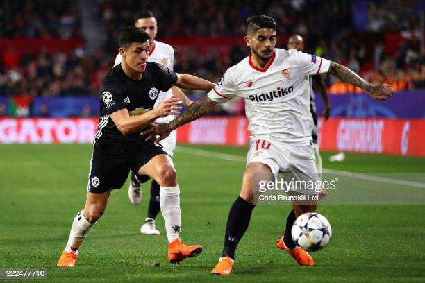 Ever Banega of Sevilla FC is challenged by Alexis Sanchez of Manchester United during the UEFA Champions League Round of 16 First Leg match between...
