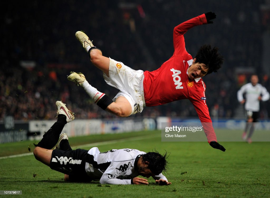 Ever Banega of Valencia brings down Ji-Sung Park of Manchester United during the UEFA Champions League Group C match between Manchester United and Valencia at Old Trafford on December 7, 2010 in Manchester, England.