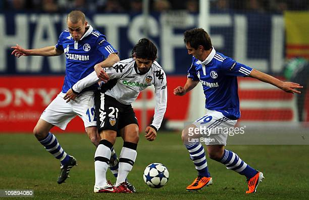 Ever Banega of Valencia is challenged by Peer Kluge and Mario Gavranovic of Schalke during the UEFA Champions League round of 16 second leg match...