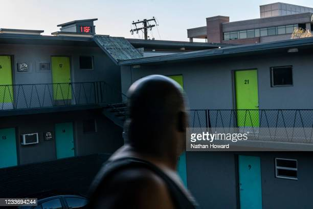 Everett Clayton looks at a digital thermometer on a nearby building that reads 116 degrees while walking to his apartment on June 27, 2021 in...
