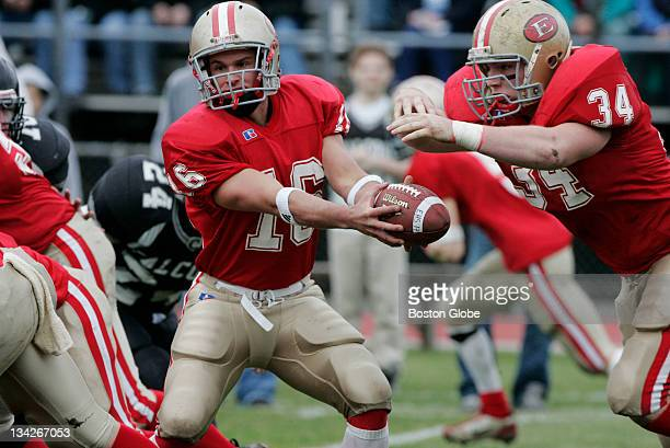 Everett High School quarterback Matthew Nuzzo #16 hands off the ball to full back Justin Sullivan #34 during the first half of their Thanksgiving Day...