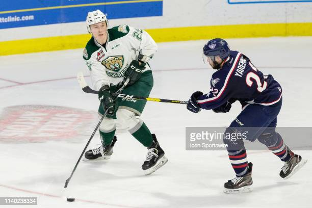 Everett Silvertips defenseman Wyatte Wylie makes a pass while being slashed on the hands by TriCity Americans forward Nolan Yaremko during Game 1 of...