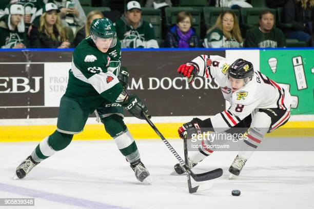 Everett Silvertips defenseman Wyatte Wylie tries to get a shot past Cody Glass of the Portland Winterhawks during a game between the Everett...