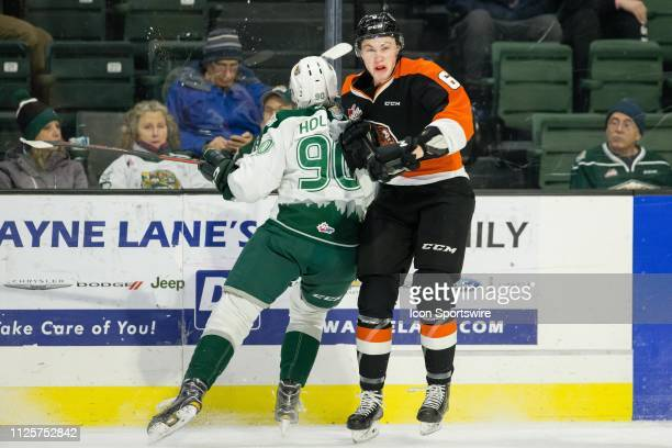 Everett Silvertips forward Robbie Holmes delivers a hit on Medicine Hat Tigers defenseman Dylan MacPherson in the first period during a game between...