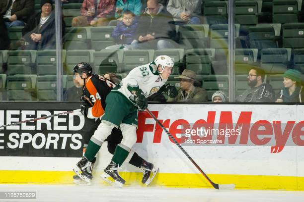 Everett Silvertips forward Robbie Holmes hits Medicine Hat Tigers defenseman Cole Clayton against the boards in the first period of a game between...