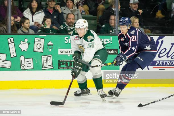 Everett Silvertips forward Robbie Holmes tries to avoid a stick check from TriCity Americans defenseman Bryan McAndrews in the third period during a...
