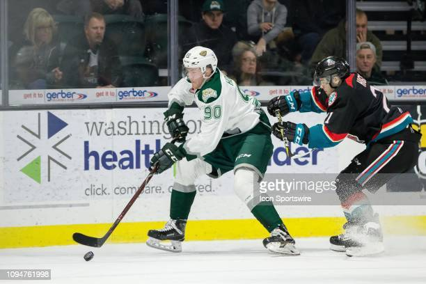 Everett Silvertips forward Robbie Holmes tries to control the puck while being cross checked by Kelowna Rockets defenseman Schael Higson during a...