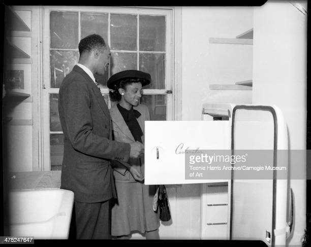 Everett Utterback showing 'Coolerator' refrigerator to Mrs Bishop Nelson Jr in kitchen of veteran's housing unit at McKinley Park Pittsburgh...