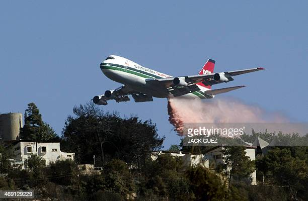US Evergreen 747 supertanker sprays over a burning area in Ein Hod in the Carmel Forest in the outskirts of Haifa on December 5 2010 as dozens of...