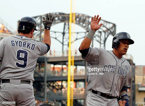 Everth Cabrera of the San Diego Padres celebrates with Jedd Gyorko after scoring on a sacrifice fly in the first inning against the Pittsburgh...