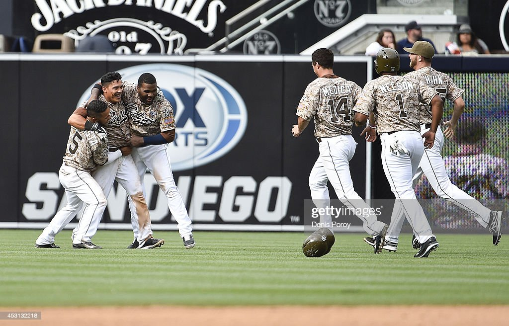 Everth Cabrera #2 (2nd L) of the San Diego Padres celebrates with teammates after hitting a walk-off single during the tenth inning of a baseball game against the Atlanta Braves at Petco Park August 3, 2014 in San Diego, California.