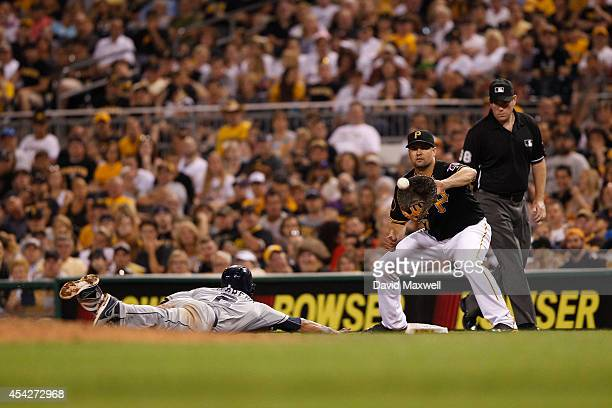 Everth Cabrera of the San Diego Padres dives safely back to first base on a pickoff attempt as Gaby Sanchez of the Pittsburgh Pirates fields the...
