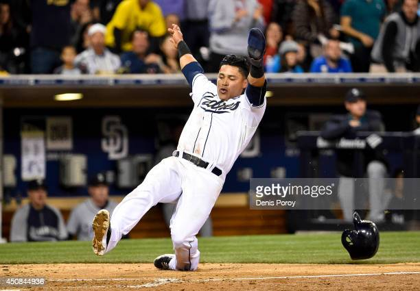 Everth Cabrera of the San Diego Padres slides as he scores during the eighth inning of a baseball game against the Seattle Mariners at Petco Park...