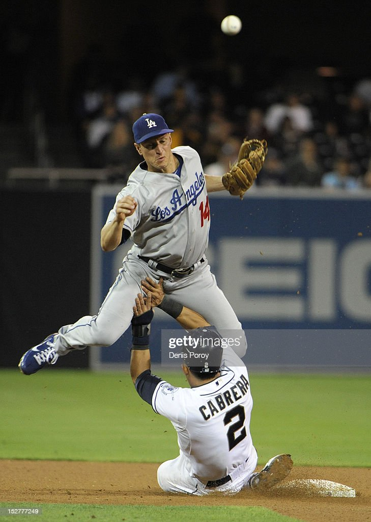 Everth Cabrera #2 of the San Diego Padres tries to break up a double play as Mark Ellis #14 of the Los Angeles Dodgers throws during the seventh inning of a baseball game at Petco Park on September 25, 2012 in San Diego, California.