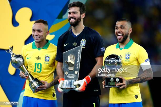 Everton, Alisson Becker and Dani Alves of Brazil pose with their trophies after winning the Copa America Brazil 2019 Final match between Brazil and...