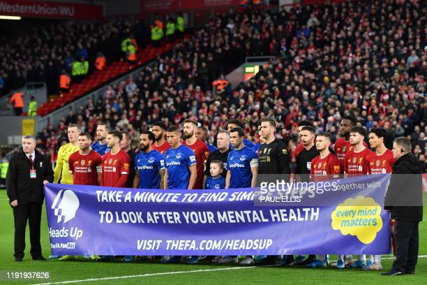 Everton and Liverpool players pose with a mental health banner before the English FA Cup third round football match between Liverpool and Everton at...