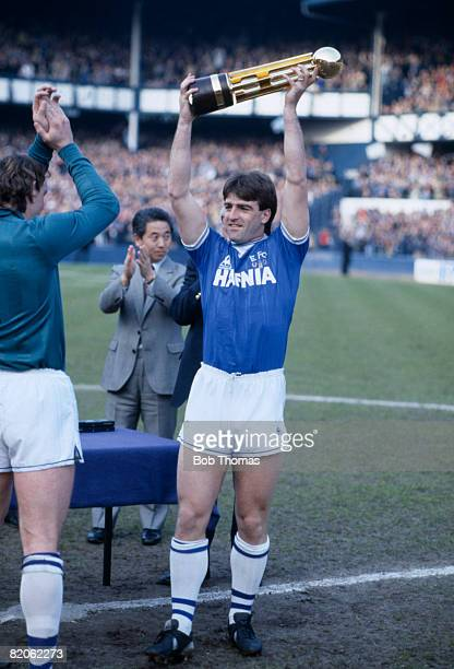 Everton captain Kevin Ratcliffe holds the Canon First Division Championship trophy aloft after the presentation ceremony prior to their match against...