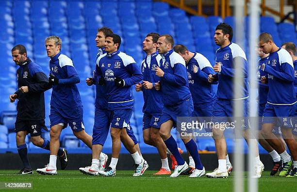 Everton captain Phil Neville along with Tim Cahill lead the pack as they jog around the pitch during warm up prior to an Everton training session at...