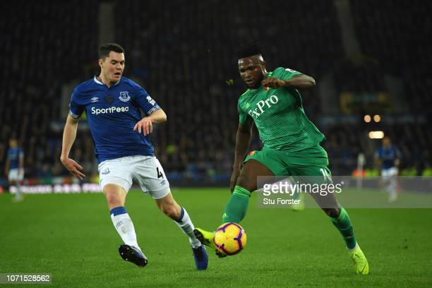 Everton defender Michael Keane jockeys Isaac Success of Watford during the Premier League match between Everton FC and Watford FC at Goodison Park on...