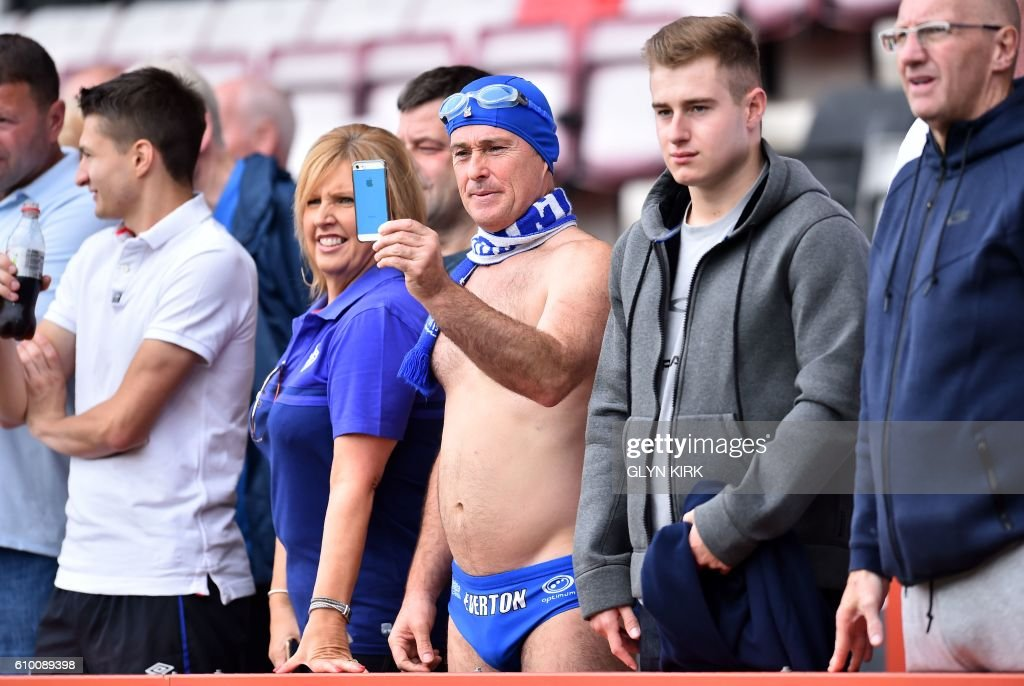 Everton fan Michael Cullen (C), known as 'Speedo Mick', poses for a 'selfie' photograph ahead of the English Premier League football match between Bournemouth and Everton at the Vitality Stadium in Bournemouth, southern England on September 24, 2016. Cullen attends Everton matches to in just his swimming trunks to raise money for charity. / AFP PHOTO / Glyn KIRK / RESTRICTED TO EDITORIAL USE. No use with unauthorized audio, video, data, fixture lists, club/league logos or 'live' services. Online in-match use limited to 75 images, no video emulation. No use in betting, games or single club/league/player publications. /