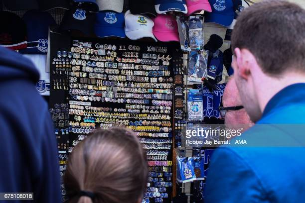 Everton fans look at pin badges prior to the Premier League match between Everton and Chelsea at Goodison Park on April 30 2017 in Liverpool England