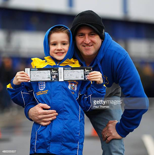 Everton fans pose with their tickets outside the ground prior to the Barclays Premier League match between Everton and Swansea City at Goodison Park...