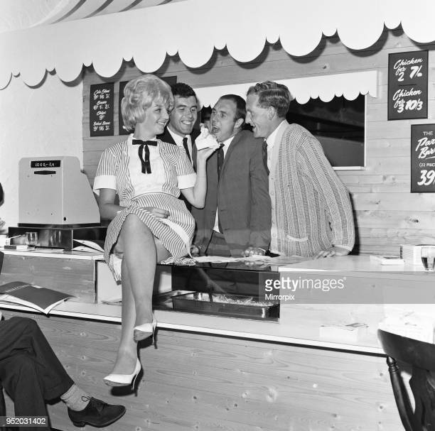 Everton football players Ray Wilson, Alex Scott and Sandy Brown being fed the house special barbecued chicken by waitress Margaret Jones after they...