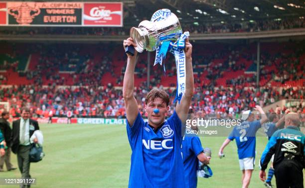 Everton forward Duncan Ferguson wearing a blue nose lifts the trophy to photographers after the 1995 FA Cup Final between Everton and Manchester...
