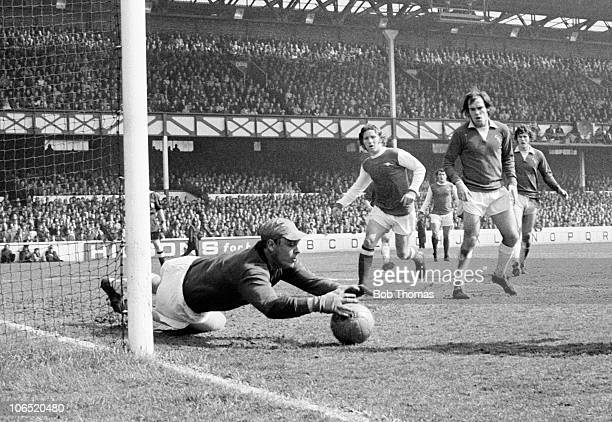 Everton goalkeeper Gordon West makes a save as Alan Ball of Arsenal runs in watched by Everton defender Terry Darracott during their Division One...