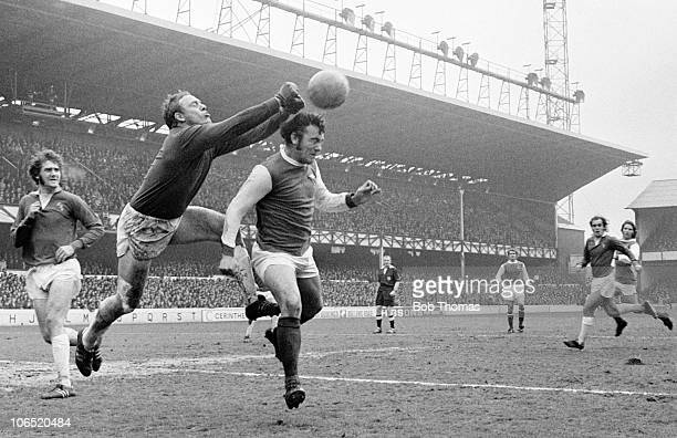 Everton goalkeeper Gordon West punches the ball away under pressure from Ray Kennedy of Arsenal as Roger Kenyon runs in to cover during their...