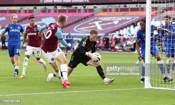 Everton goalkeeper Jordan Pickford gets to the ball ball before Jarrod Bowen of West Ham United to make a save during the Premier League match...