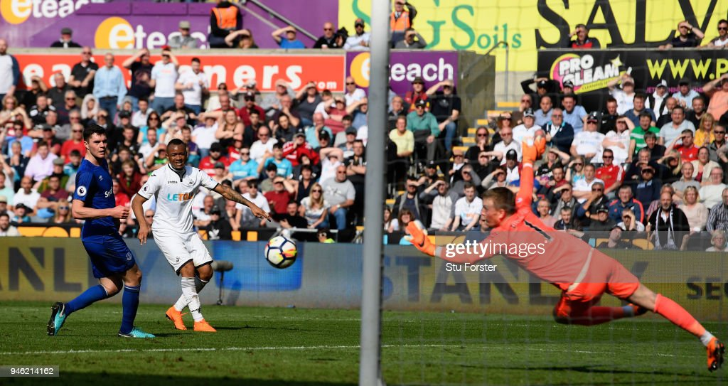 Everton goalkeeper Jordan Pickford is beaten for the Swansea goal by Jordan Ayew (c) during the Premier League match between Swansea City and Everton at Liberty Stadium on April 14, 2018 in Swansea, Wales.