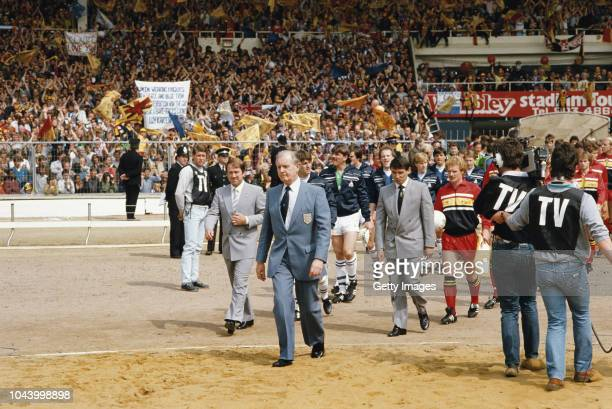 Everton manager Howard Kendall and his team and Wwatford manager Graham Taylor and his Wwatford team are led onto the pitch through the sand by an FA...