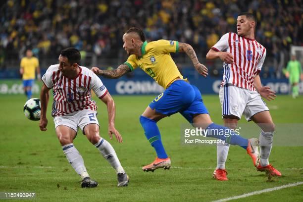 Everton of Brasil gets through between Ivan Piris and Richard Sanchez of Paraguay during the Copa America Brazil 2019 quarterfinal match between...