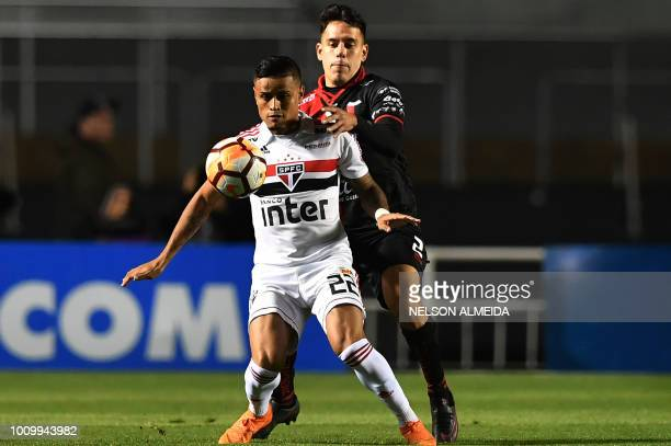 Everton of Brazil's Sao Paulo is challenged by Gustavo Toledo of Argentina's Colon de Santa Fe during their Copa Sudamericana football match at the...