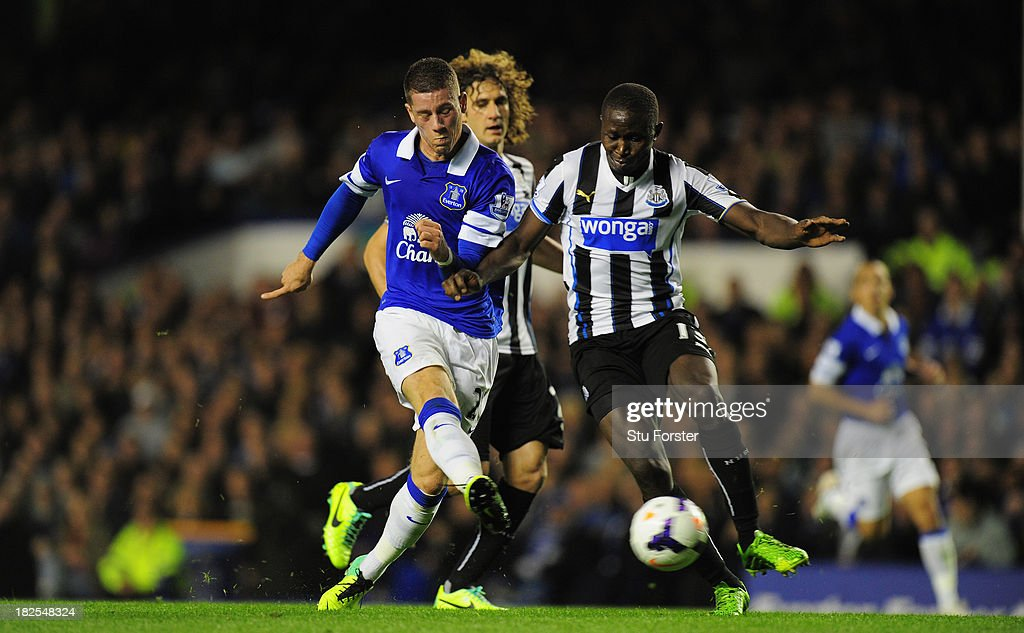 Everton player Ross Barkley shoots past Mapou Yanga-Mbiiwa to score the second goal during the Barclays Premier League match between Everton and Newcastle United at Goodison Park on September 30, 2013 in Liverpool, England.