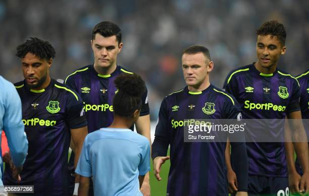 Everton player Wayne Rooney shakes the hand of the mascot before the Premier League match between Manchester City and Everton at Etihad Stadium on...