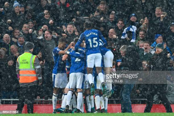 Everton players celebrate after Everton's English striker Wayne Rooney scored an equalising goal from the penalty spot to make the score 11 during...