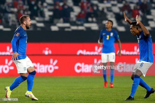 Everton Ribeiro of Brazil celebrates with teammate Alex Sandro after scoring the first goal of his team during a match between Chile and Brazil as...