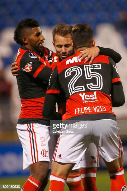 Everton Ribeiro of Flamengo celebrates with Rodinei and Felipe Vizeu after scoring the fifth goal of his team during a match between Palestino and...