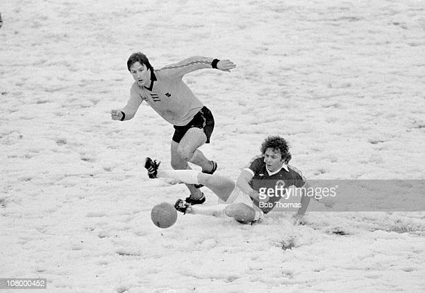 Everton striker Andy King slides in to tackle Steve Daley of Wolverhampton Wanderers during their First Division match played on a snow covered pitch...