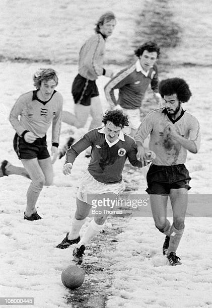 Everton striker Mickey Walsh is challenged by Wolverhampton Wanderers defender George Berry during the First Division match played on a snow covered...