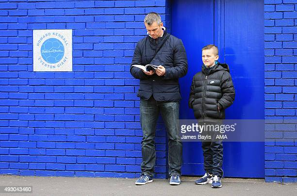 Everton supporters read the matchday programme stood outside Goodison Park next to a plaque dedicated to former Everton manager Howard Kendall during...
